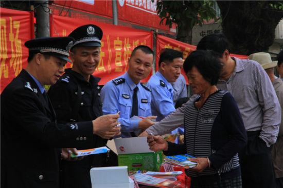 工作人员向过往群众发放《宪法与我》,《海南省法制宣传教育条例》