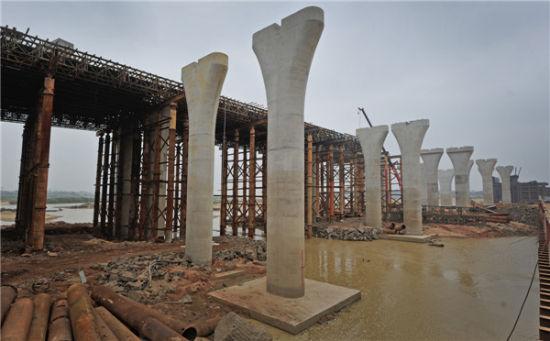 一座木桥,横跨南渡江,20多年来,一直是东山镇马坡村、东仓村与定安县定城镇互通的重要交通枢纽。木桥虽有安全隐患,但每天仍有4000人次往返。   而今,在这座跨江木桥上游约1公里处,一座在建的宏伟跨江新桥日见雏形。它的出现不仅让跨江木桥即将成为历史,更重要的是方便和确保了周边30万人的出行安全,助推海口、定安两地的经济发展。   新桥预计明年底开通   几个工人将整理好的钢管绑好,再由吊机运往桥面;不远处的几台挖掘机正在填土筑建施工平台,一些工人在整理钢筋12月23日上午10点多,定海大桥施工现场,