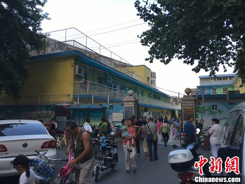 北京某幼儿园门口,家长接孩子放学.汤琪