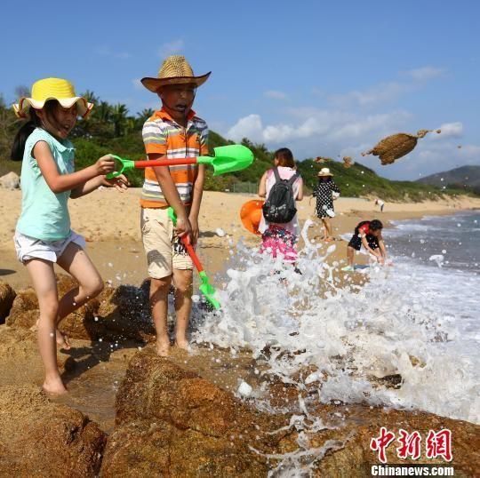春节假期过后,小朋友在南山景区海边戏水玩耍. 陈文武 摄