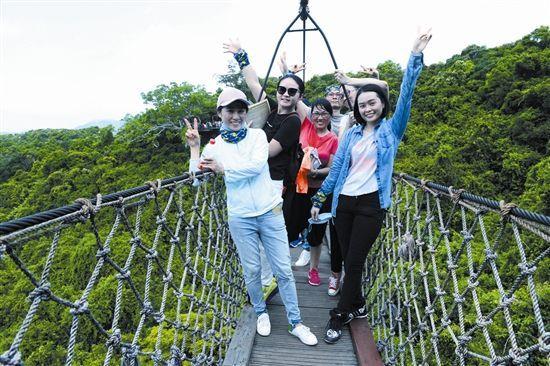 5月25日,一群年轻游客愉快地在亚龙湾热带天堂森林旅游区开展雨林拓展